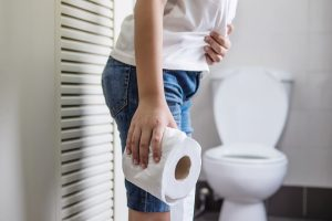 Asian boy sitting on toilet bowl holding tissue paper  - health problem concept