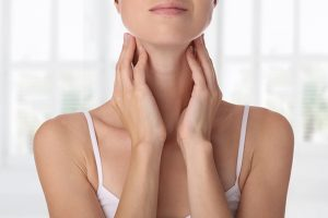A-woman-with-thyroid-issues-holds-her-neck.